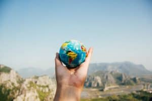 Hand holding up small globe